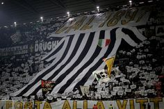 Juventus' supporters hold a giant Juventus jersey during the Italian Serie A football match between Juventus and As Roma on December 17, 2016 at the Juventus Stadium, in Turin. / AFP / MARCO BERTORELLO