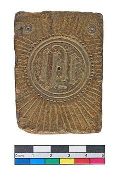 #english #object 15c Honestone mould for casting lead badges; quadrangular; circle of dots, radiae proceeding from it; sacred monogram.