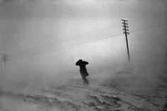 Josef Koudelka ALBANIA. 1994. Snow blizzard on the road to Korce. An Albanian braves the weather.