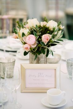 Framed table names as song titles - Image by Hayley Savage Photography - Pronovias 'Leonela' Wedding Gown & Coast Bridesmaid Dresses with No.1 by Jenny Packham Accessories in a Marquee at Hill Place with Pink & Grey Colour Scheme & Church Flower Arch.