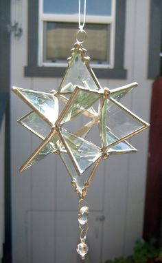 A Clear Beveled Stained Glass three dimensional 12 point Star suncatcher. It is approximately 7 long by 5 wide and is copper foiled constructed.