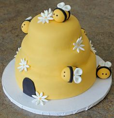 Red Velvet with cream cheese filling covered in a golden yellow fondant shaped like a beehive. Fondant bumblebees and daisies accent the cake.