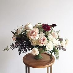 Winter floral arrangement of blush quicksand roses, white majolika spray roses, burgundy dahlias, privet berry, and eucalyptus in a Campo de' Fiori aged terra cotta Venetian fruit bowl | Flowers and Photo by Wild Green Yonder