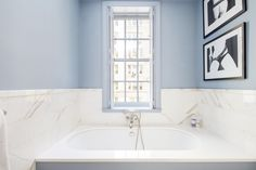 Bathroom with baby blue walls, graphic art, and a marble tub