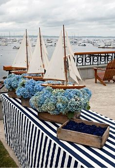 WEDDING Cocktail Hour Decor ~ Wooden sailboats float on arrangements of sea blue hydrangeas. For a nautical wedding