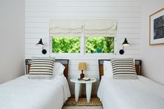 """One of McKinley's favorite rooms also happens to be one of the house's smallest. This guest room, despite its challenging square footage, feels airy and fresh, in part because of the white shiplap walls. The entire home is painted in Whitewater Bay by Benjamin Moore. """"At the beach, you have to make sure you pick the right white that has a little bit of pink in it to warm things up and reflect light beautifully,"""" he says. Sconces from Rejuvenation hang over the vintage Italian iron-and-rattan…"""