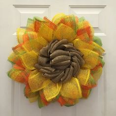 This is a paper mesh creation of multi colors and patterns. The main colors are Yellow, Orange, Green and Brown Burlap. This wreath measures out to about 24 in diameter and is not a weather durable product, you will need a covered porch for this wreath, this is not weather proof since it is made of paper mesh. This wreath cannot get wet and may fade if in direct sunlight. Please note that anytime you cut paper mesh there will be some fraying.