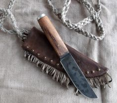 Primitive Mountain Man knife with wormy chestnut wood, reclaimed from an old barn . Over the shoulder carry tacked and fringed sheath with hand woven hemp strap. By Miss Tudy and Bud of Out of the Ashes Forge. https://www.etsy.com/shop/misstudy