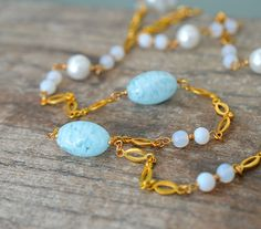 Long fancy link gold chain necklace embellished with pale blue Italian Murano glass and vintage Japanese glass beads. This delicate necklace is perfect for spring and summer and is so versatile - wear it to the office or weekend brunch - wear it long or doubled! The three Venetian glass beads that are the star of this necklace are just stunning! The pale blue glass is mottled with white glass....look closely and you will see blue sky with fluffy white clouds! The smaller slightly opalescent…