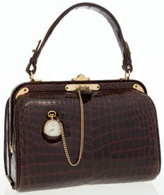 This whimsical Lederer classic structured satchel style bag is done in shiny brown crocodile that is accented with gold hardware, and an attached pocketwatch.