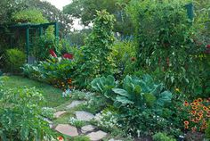 Use strong lines and vertical elements:The stepping stones draw the eye into the space and prevent the path from getting worn or muddy. The clean edge of the small lawn leads the eye further into the garden, where a sculptural red rooster waits. Arbors frame the scene. The bed of beans, squash, strawberries, tomato and collards features contrasting foliage sizes, adding texture and interest