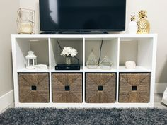 #KALLAX #shelving from #IKEA used as a TV stand, featuring #KNIPSA #baskets with #gold and #white accents.