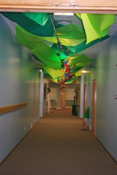 Jungle Jaunt hallway. Green plastic table runners crisscrossed across the ceiling and brown paper vines hung down the middle. We hung some foam parrots and inflatable monkeys to complete the look.