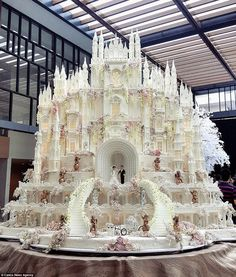 This extravagant cake is an epic castle, and looks like it came straight out of Cinderella as the scene even features the fictional princess' famous glass carriage at the foot of stairs. The whole thing has been made out of edible fondant icing and sugar