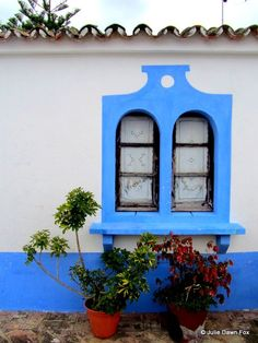 Blue paintwork around a pair of small arched windows in a traditional Portuguese cottage, Alte