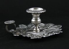 Grande e importante palmatória em prata de lei em formato de folha com pega simulando corpo de serpente.  Brasil, sec. XIX. 19 cm de comprimento. 332 g.