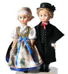 """Lalki w Stroju Cieszyńskim  odświętny strój kobiecy: składa się z nakrycia głowy (zawiązywana chustka z koronkowym """"naczółkiem""""), """"kabotka"""" tj. krótkiej białej bluzki z żabotem pod szyją i ozdobną broszką, sukni wykończonej dołem """"galonką"""" tj. jedwabną wstęgą najczęściej niebieską lub czarną, """"żywotka"""" czyli gorsetu przyszytego do przymarszczonej spódnicy, zapaski czyli fartuszka z wzorzystej tkaniny i ozdobnej wstążki zawiązanej w pasie. """"Żywotek"""" najczęściej z aksamitu lub z sukna bogato…"""
