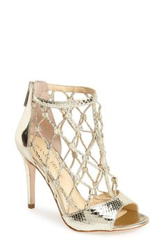 Obsessed with the latticework straps on these gold open-toe booties.