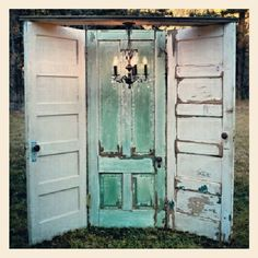 3 old doors hinged together with a chandelier hanging above vignette is a great store display or could be a Photo prop background for vintage wedding or used for a trade show or craft Booth display.  Repurpose, upcycle, recycle, salvage, diy!  For ideas and goods shop at Estate ReSale & ReDesign, Bonita Springs, FL