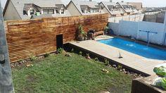 Piscina en desnivel, con deck de madera en suelo y pared para la privacidad.