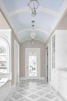 Elegant blue and gray master bathroom boasts a sky blue barrel ceiling accented with white molding and illuminated by glass bell jar lanterns hung over white and gray marble diamond pattern floor tiles leading to a leaded glass bathroom door.