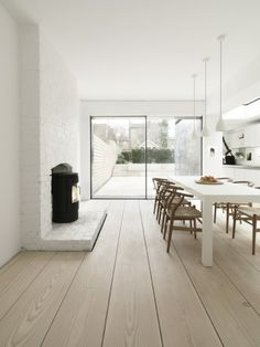 Long table with chairs, clean white walls.