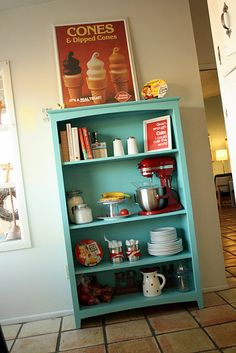 Fun color! And great idea using a bookcase in the kitchen.