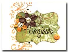 Instructions:  Cut a tag from pattern paper using a die cut machine.   Stamp Bonjour with brown ink onto the tag.   Stamp the Dot Flourish border with Soft Apricot ink onto a white card.   Affix the tag in place.   Add flowers, buttons and gems.