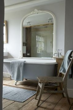 White bathroom, large mirror framed in white, claw foot tub