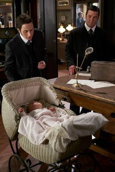 Roland keeps an eye on Crabtree (Jonny Harris) as he and Murdoch (Yannick Bisson) discuss the case