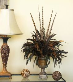 An elegant bouquet of brown coque feathers accented with pheasant feathers arranged in a brushed metal finish resin vase.