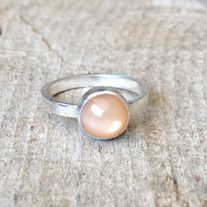 A 7mm peach moonstone has been set in sterling silver and sits on a sterling silver ring band. This ring is simple, elegant and can be stacked with others. The moonstone changes hues when it catches the light and is luminescent. This ring is also available in a purple gray moonstone-see separate ...