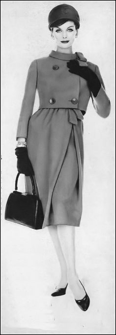 Anne St. Marie in suit of a clear red worsted with short jacket barely skimming the skirt-top by Dan Millstein, hat by John Frederics, Lucille handbag, photo by Karen Radkai, Vogue, November 1, 1958