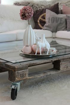 Add castors to a recycled shipping pallet, and top with a sheet of glass to make a high impact coffee table.