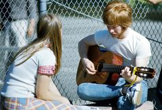 A young man plays guitar as a young woman sits and listens. Photo taken between 1975 and 1977. (By Neil House, courtesy of Everett Public Library)