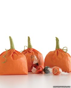 Pumpkin Treat Bags*Fill orange mini craft bags with candy. Twist the top of the bag up into a stem. Pull floral tape off roll and stretch it so it becomes sticky. Wrap floral tape around stem, starting at the top and moving downward. Rip off take, leaving 3 to 4 extra inches hanging on the bottom. Twist extra tape into tendril, wrapping it around finger until it curls.