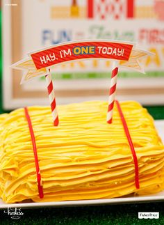 """This hay bale smash cake is extra fun and farm-friendly — perfect for a first birthday barnyard bash! For the finishing touches, top with a cheeky """"Hay, I'm ONE today!"""" banner."""