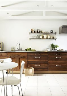 Dark raw wood cabinets with a stainless steel countertop - No upper cabinets, instead, open shelving for storage - Neutral, fresh, modern kitchen