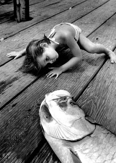 Alfred Eisenstaedt  Looking at the mouth of a big fish that daddy had just caught, Florida, 1956