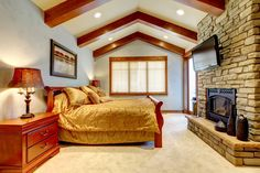 Expansive master bedroom with vaulted ceiling and exposed beams with brick wall framing gas fireplace