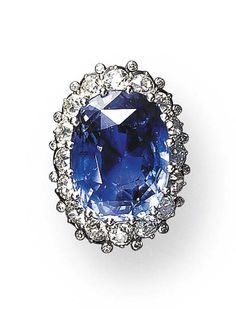A SAPPHIRE AND DIAMOND RING, BY SEAMAN SCHEPPS Set with an oval-cut sapphire weighing approximately 23.40 carats, with an old European-cut diamond frame, accented by diamond collets, mounted in platinum, in a leather box Signed Seaman Schepps