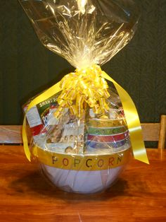 """Movie Gift Basket: I made this movie gift basket for my niece's wedding shower as a door prize. I found a large plastic """"popcorn"""" bowl with a matching set of serving bowls and used the big bowl as the container. Inside are the serving bowls, candy, microwave popcorn, popcorn topping (cheese flavoured) and a 3 in 1 movie DVD - all romantic comedies with a wedding theme. LOL! Popcorn Toppings, Popcorn Bowl, Microwave Popcorn, Movie Basket Gift, Movie Gift, Bridal Shower Prizes, Towel Cakes, Door Prizes, Crafty Projects"""