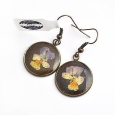 Small, dangle earrings made ​​of transparent resin, in which I embedded real, pressed pansy flowers collected by me in Poland in 2014. I made only one