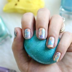 This swirly Easter egg dyed manicure was created using a water marbling nail art technique