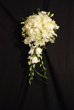 Beautiful cascade of white dendrobium orchid, white roses, white lisanthus and white hydrangea.