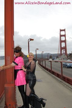 Mistress AliceInBondageLand ties her sissy slave to the Golden Gate Bridge in kinky San Francisco, California for the public humiliation exposure of his lifetime. This humiliated crossdresser is strapped to the public monument wearing a latex sissy maid uniform made out of NEON PINK rubber. Cars honk their horns as they go past the spectacle, but the cops tell us to carry on as long as we aren't causing permanent damage. Now my slutty tv cd won't misbehave again after this public punishment!!!