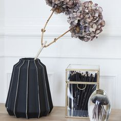 Hubsch Large Black & White Fluted Vase: These beautiful matt black vases have a subtle white detail and a classic shape. They are equally stunning with or without flowers. This product is the larger vase on the left hand side of the image.