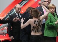 Russian President Vladimir Putin tactfully ignoring the sudden appearance of a topless protestor.