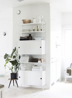 White wire shelving unit with integral cupboards