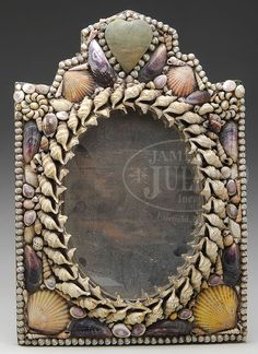 "OUTSTANDING SHELL DECORATED MIRROR. Mid 19th century, Maine or New England. The graphic native seashell design achieved with matching shell forms centering an oval mirror plate beneath a heart shaped pin cushion within the shell crest, all mounted on a heavy fiber or cardboard backing. SIZE: 15-1/2"" h x 11-3/4"" w. CONDITION: Shell work very good and original. Fold out rear stand, now weak from age/use. Mirror suitable for wall mounting. 9-27788 (800-1,200)"